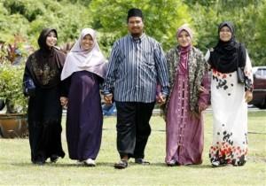 In this  Aug. 15, 2009 photo, polygamist Mohammad Inaamulillah Bin Ashaari, center, is shown with his four wives, from left, Rohaiza Esa, Ummu Habibah Raihaw , Nurul Azwa Mohd Ani,and Ummu Ammarah Asmis at the